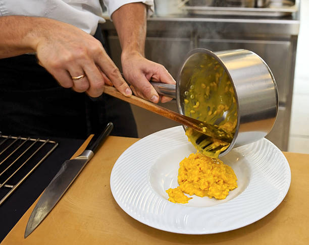chefkoch putting-risotto auf teller - safransauce stock-fotos und bilder