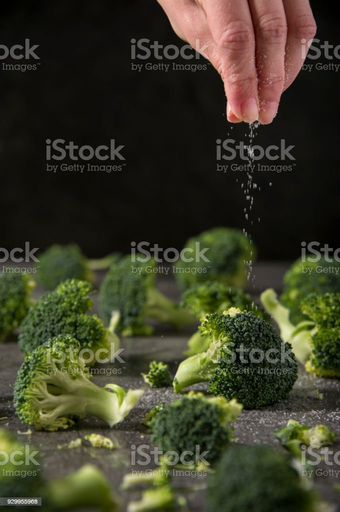 Chef is salting grilled broccoli pieces on the kitchen table. stock photo