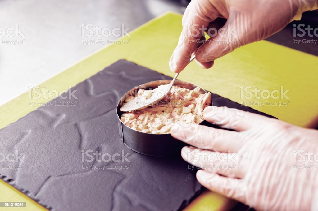Chef is serving starter dish with metal ring, toned royalty-free stock photo