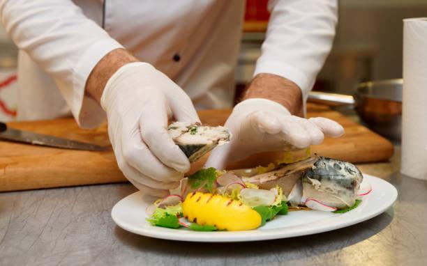 küchenchef ist gedämpfter fisch servieren. - italienische küchen dekor stock-fotos und bilder