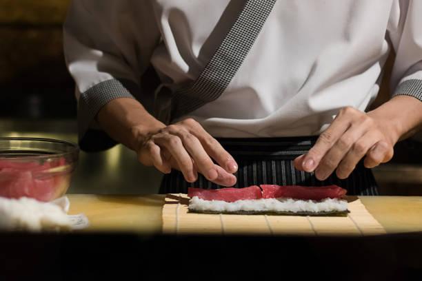 chef japanese cuisine in hotel or restaurant kitchen cooking, only hands. he is working sushi - teppan yaki grill stock-fotos und bilder