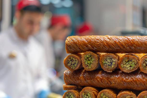 Chef haciendo baklava con nueces en el restaurante. - foto de stock