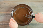 istock Chef Making Chocolate Donuts Batter by using whisk. Egg yolk used for preparing doughnuts 947772408
