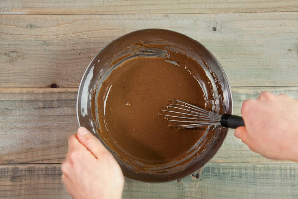 koch machen schokoladen donuts teig mit schneebesen. eigelb, verwendet für die zubereitung von donuts - hausgemachte gebackene donuts stock-fotos und bilder