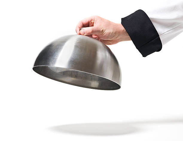 Chef opening cloche lid stock photo