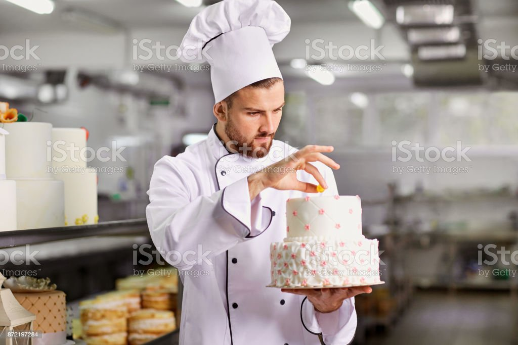 Chef pastry decorates cake in the kitchen. stock photo