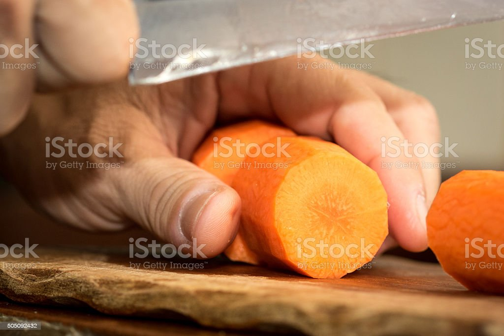 Chef peeling carrot with Knife. stock photo
