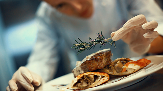 Closeup tilt of blurry female chef placing rosemary on a steak meal before serving. She's using protective gloves when dealing with ready to eat food.
