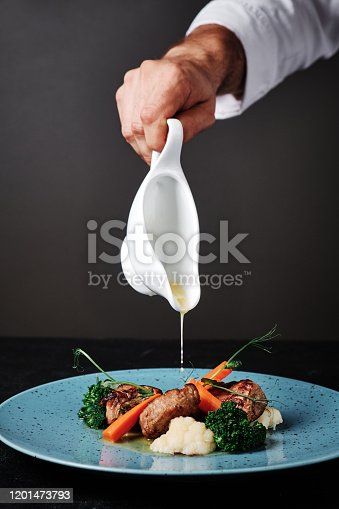 Chef plating up food in a restaurant pouring a gravy or sauce over the meat salad before serving it to the customer, close up view of his hand and the gravy boat