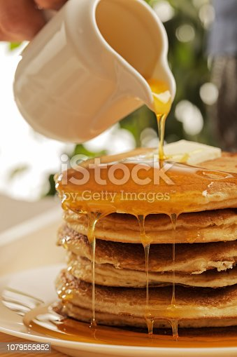 Chef pouring maple syrup over stacked pancakes with blueberries on top and cream on the side. Selective focus