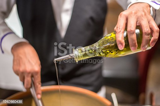 Chef pouring olive oil to the bowl