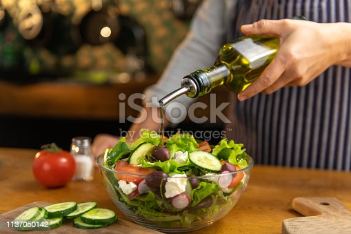 Chef pouring salad oil