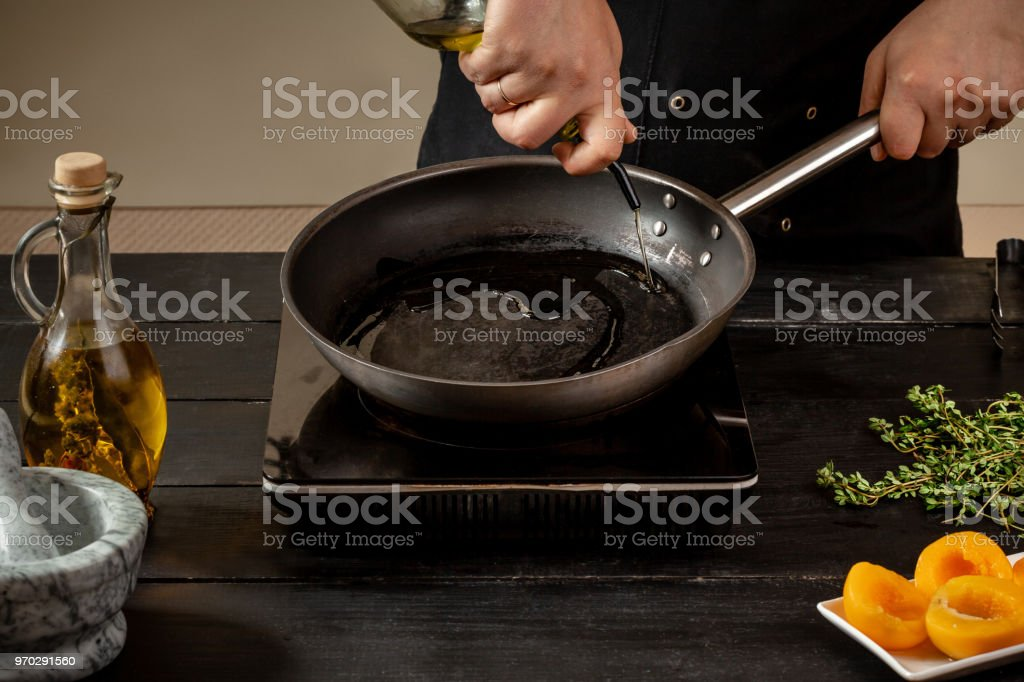 Chef pours olive oil in a pan for making new dish. Wooden table....