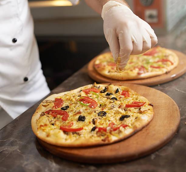 chefkoch tropfen gewürze auf pizza - frucht pizza cookies stock-fotos und bilder