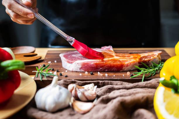 주방에서 바비큐 소스를 곁들인 돼지고기 다진 스테이크를 준비하는 셰프 - 양념에 재기 뉴스 사진 이미지