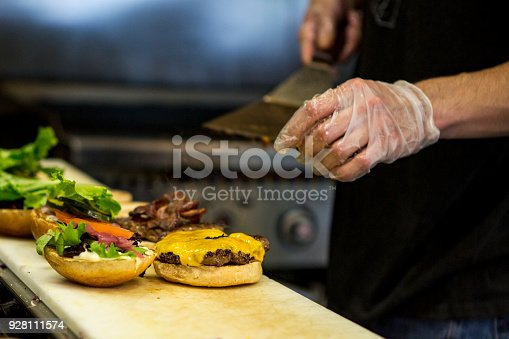 On a restaurant kitchen counter a chef prepares multiple hamburgers