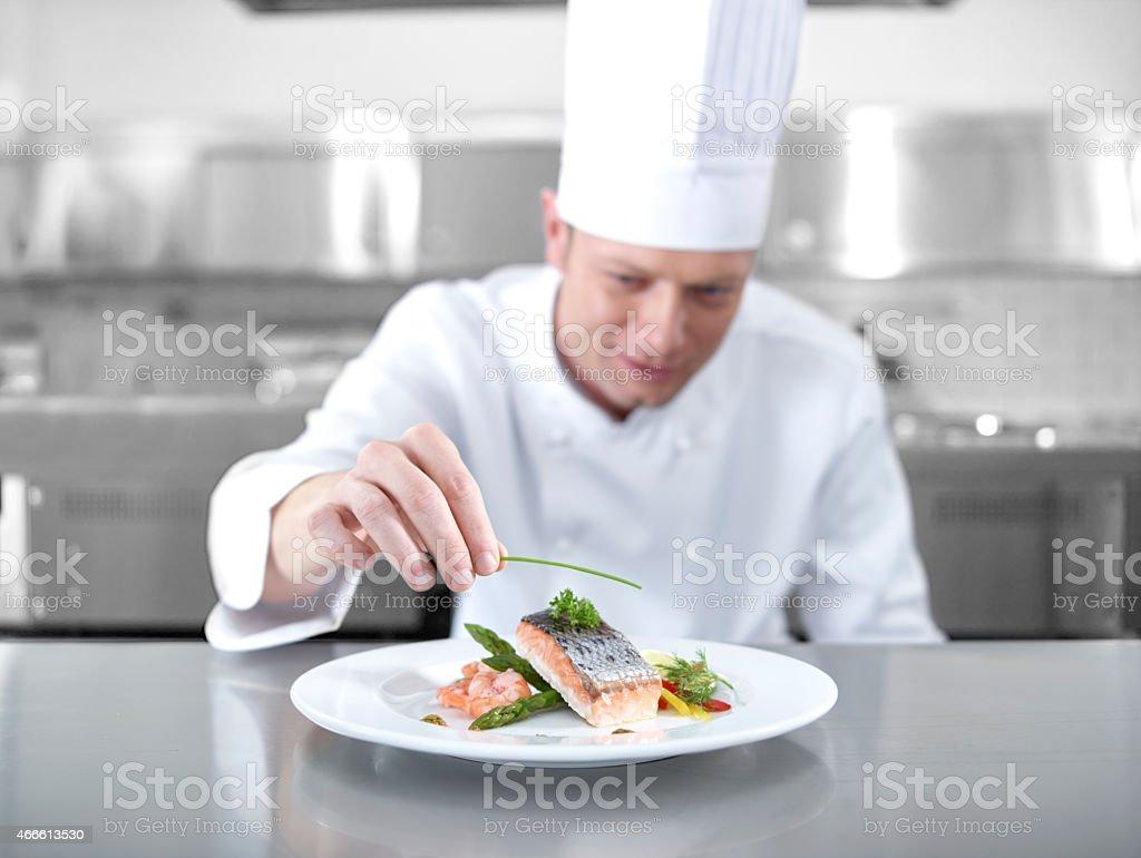 Chef preparing a main dish of fish stock photo