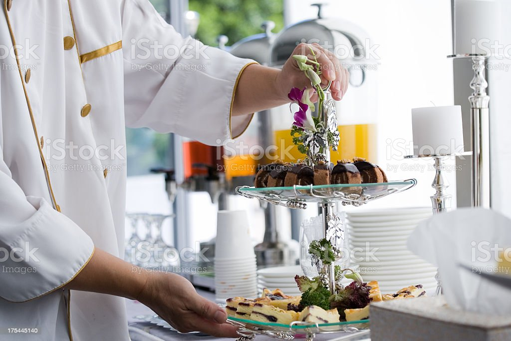 A chef preparing a stand of afternoon wedding tea cakes stock photo