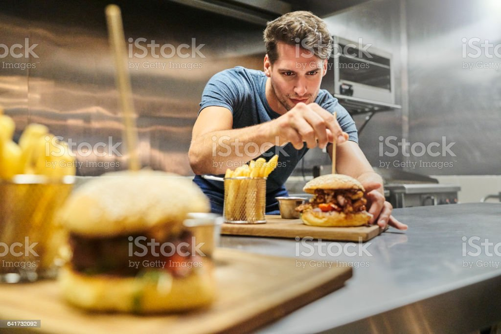 Chef preparing burger on plate at restaurant stock photo