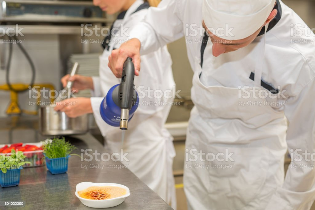 Chef preparing creme brulee stock photo