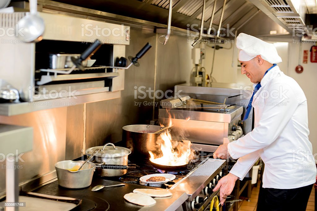 Chef preparing  cuisine in hotel kitchen royalty-free stock photo