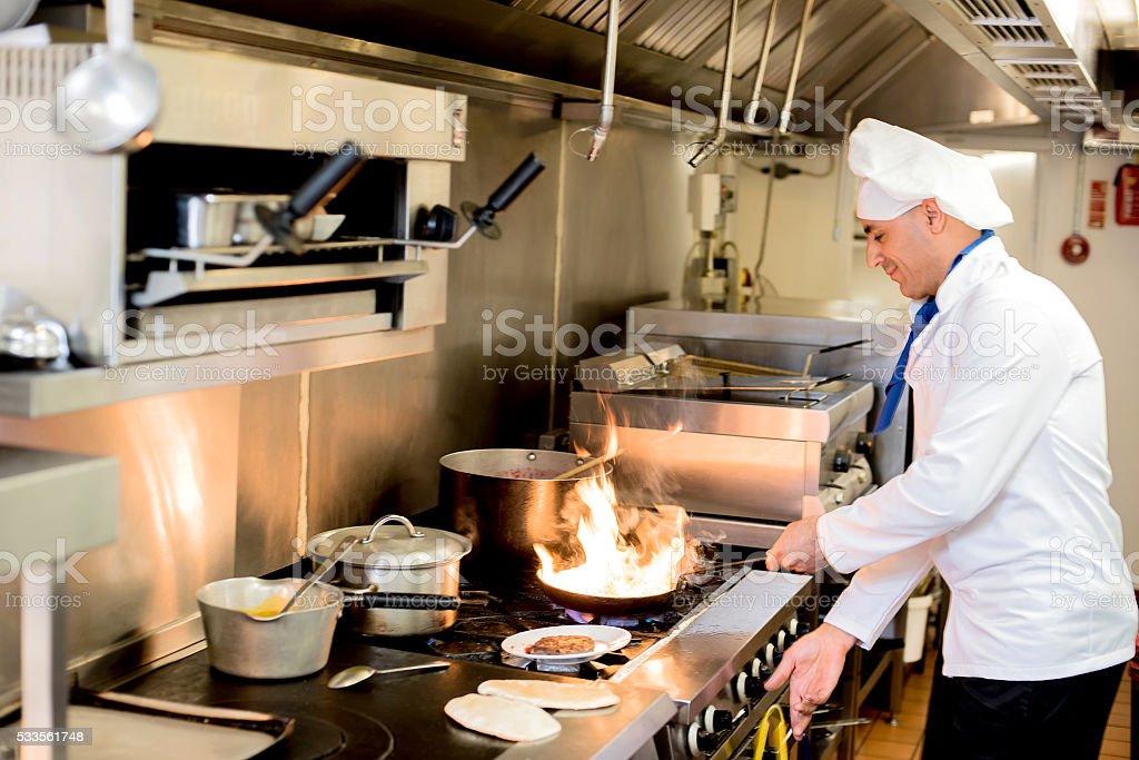 Chef preparing  cuisine in hotel kitchen stock photo