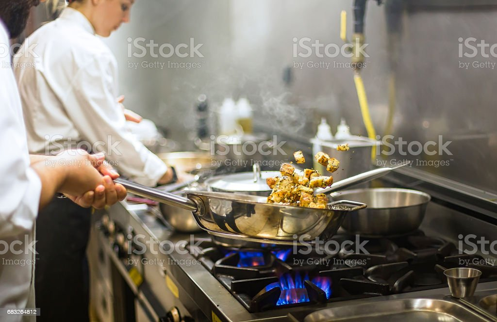 Chef preparing cuisine in hotel kitchen stock photo