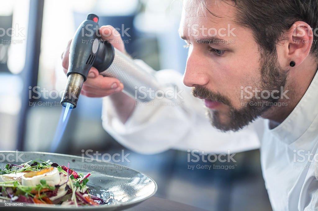 Chef preparing food. Cook flamed using Flambe gun pistol. stock photo