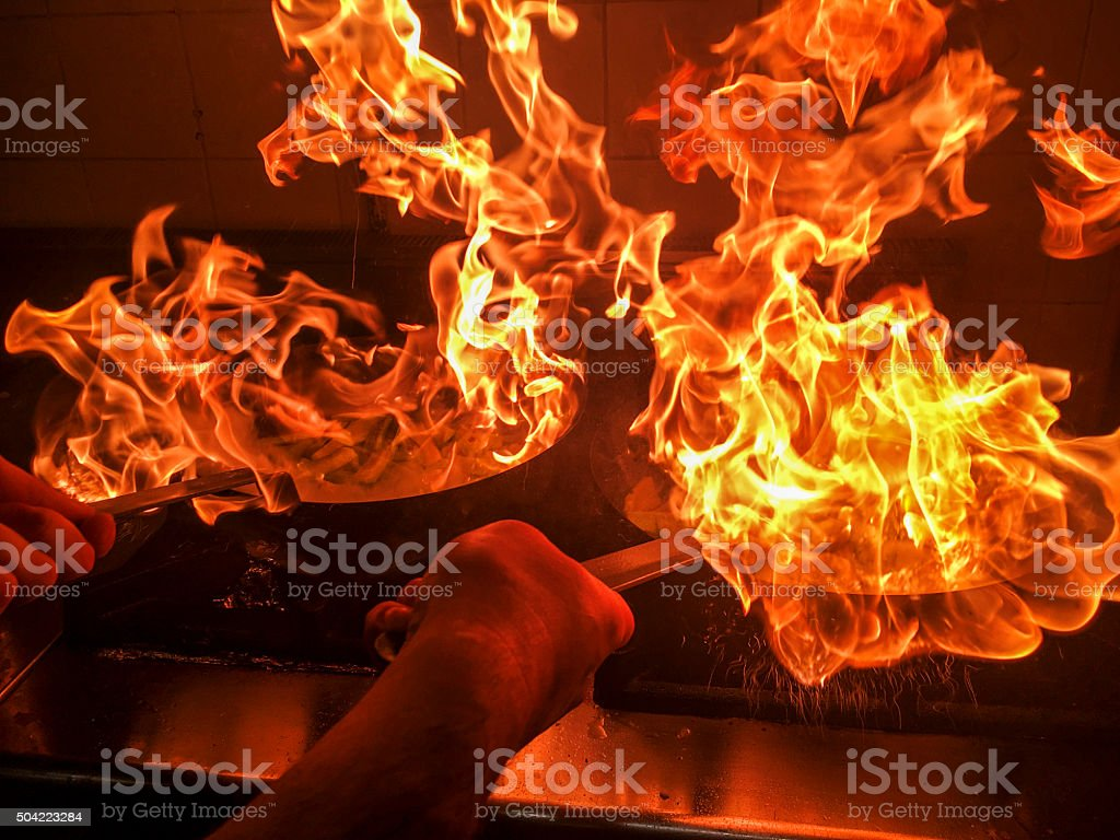 Chef preparing food in a pan in flames stock photo