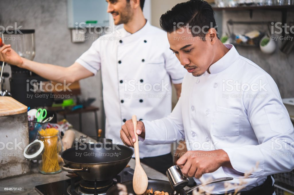 chef preparing food in the kitchen of a restaurant stock photo