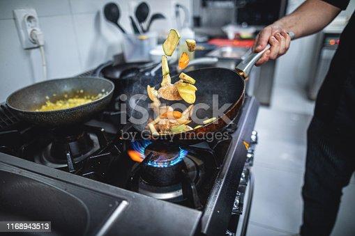 Skilled chef preparing gourmet food at a restaurant kitchen.