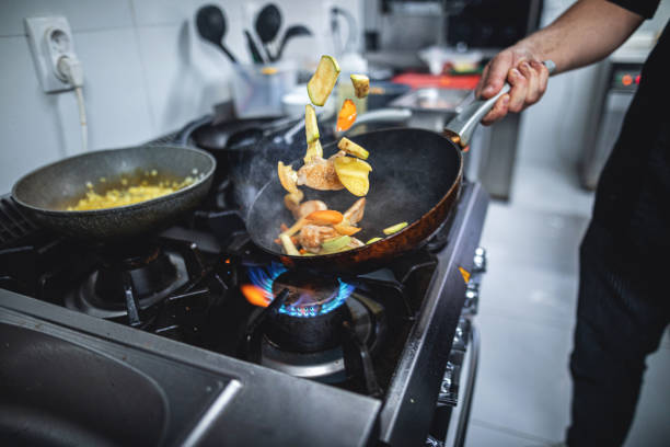 Küchenchef bereitet Essen über einem brennenden Gasherd zu – Foto