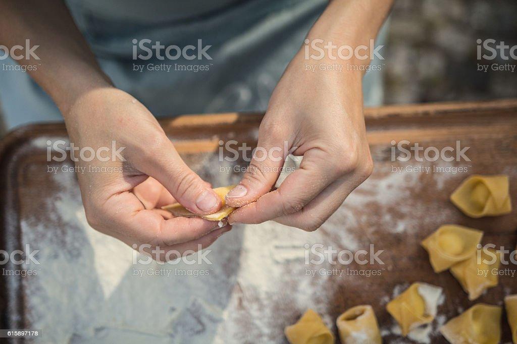 chef preparing handmade stuffed pasta tortellini stock photo