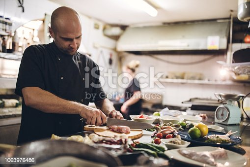 Young Chef Preparing Meal In Kitchen Restaurant