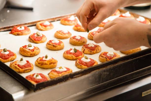 koch bereitet minipizzen - italienische küchen dekor stock-fotos und bilder