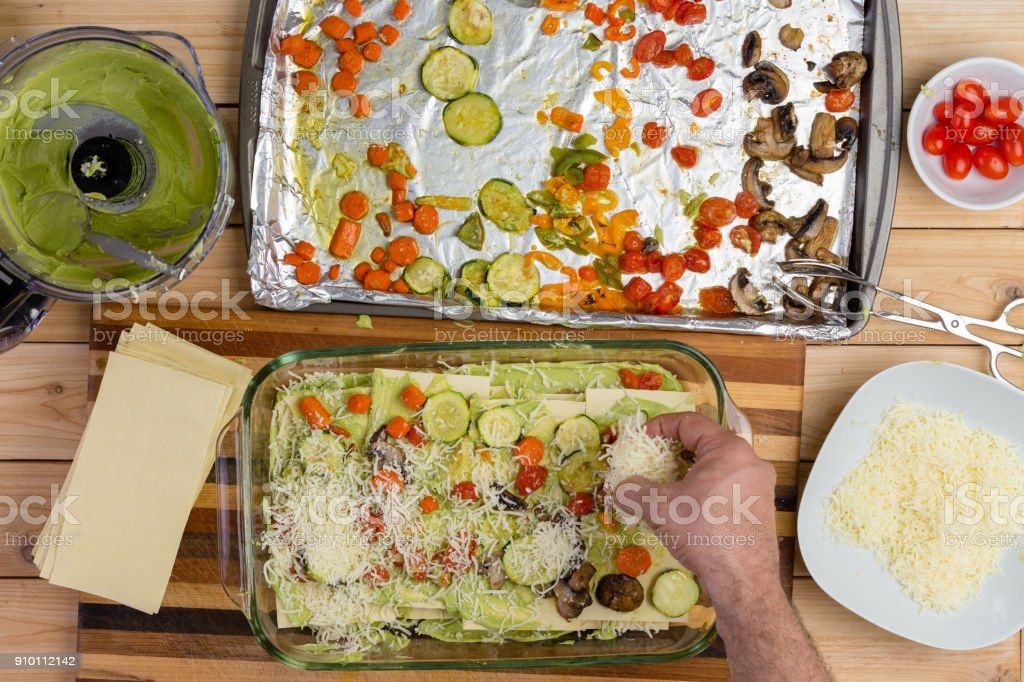 Chef preparing vegetable lasagne adding cheese stock photo