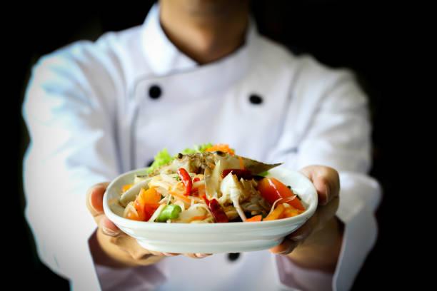 chef-kok met trots presenteren thaise pittige krab papaya salade - lao, isan-keuken - krab gerecht stockfoto's en -beelden