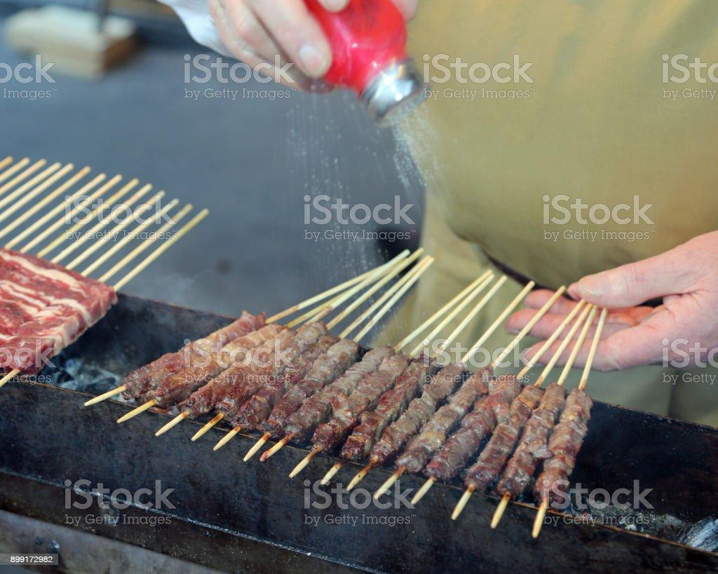chef put salt on Meat called Arrosticini in italian language a traditional italian cuisine of Abruzzo Region - foto stock