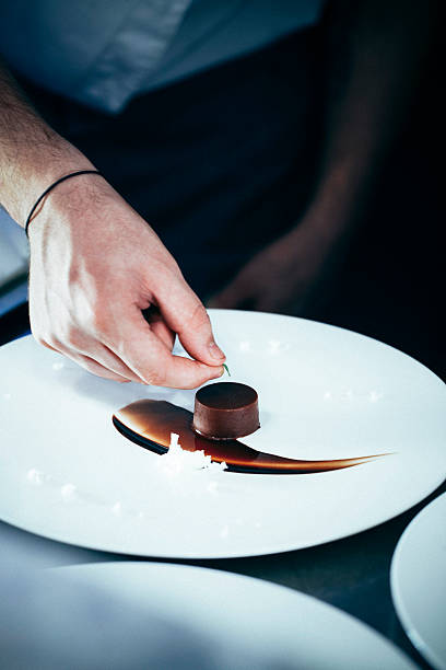 Chef putting a green leaf on chocolate dessert stock photo