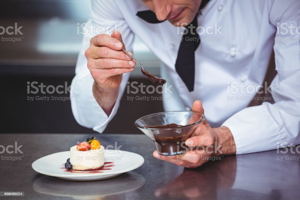 Chef putting chocolate sauce on a dessert stock photo