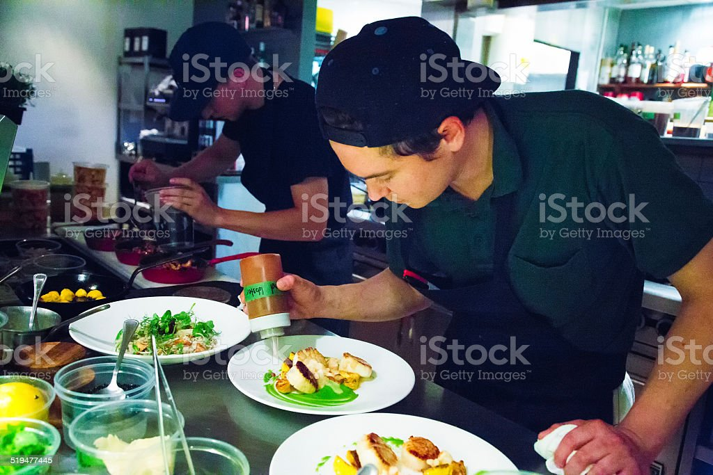 Chef putting finishing touches to plating his dishes stock photo