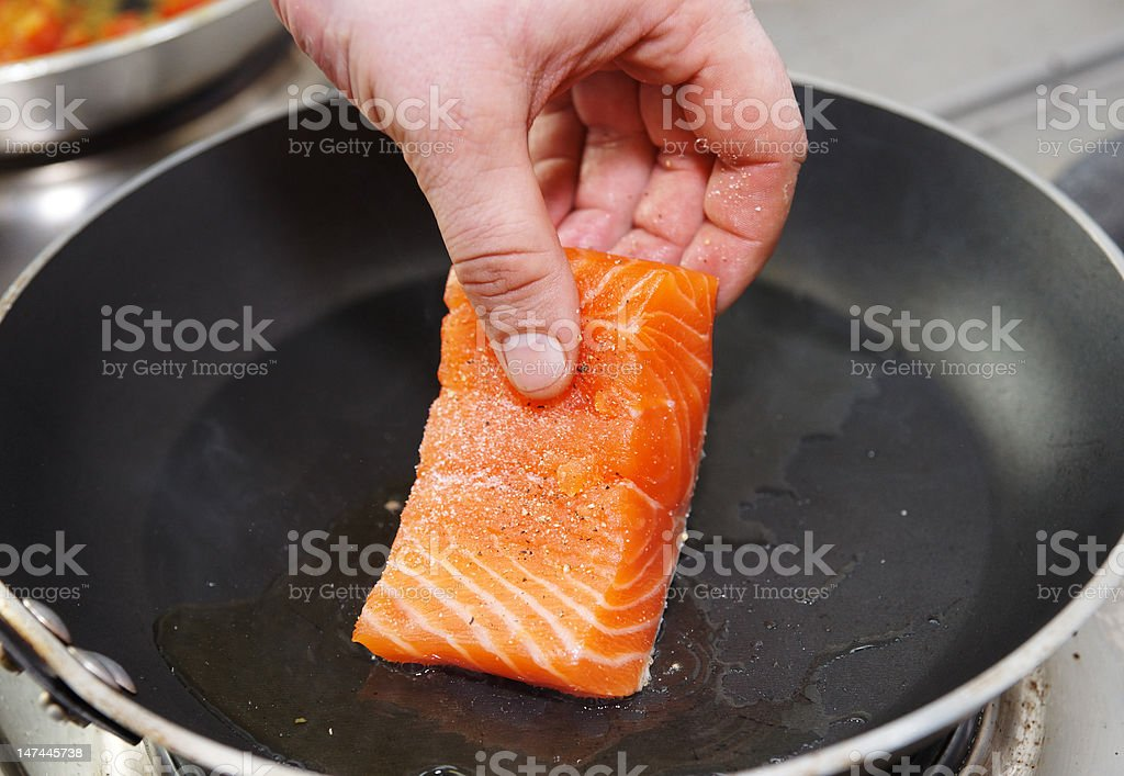 Chef putting salmon fillet on hot pan stock photo