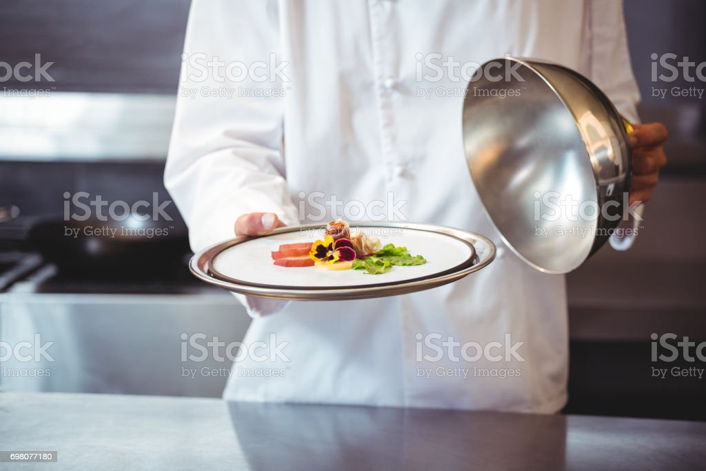 Chef raising a bell of a dish stock photo