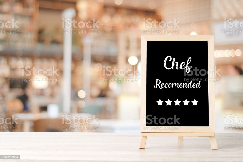 Chef recommend and five star on blackboard standing over blur restaurant background, copy space for text, food and drinks background, banner stock photo