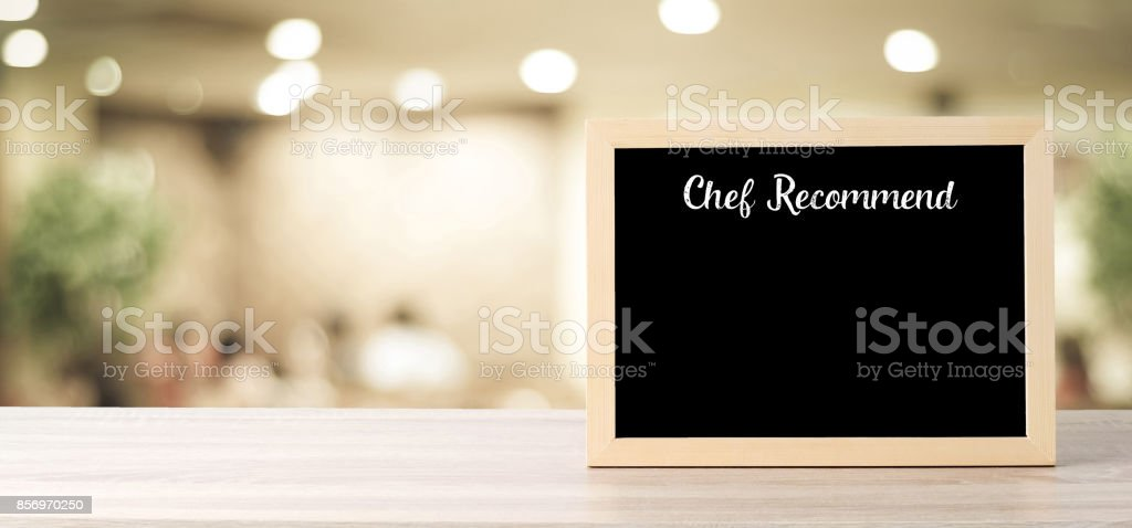 Chef recommend on blank blackboard standing over blur restaurant background, copy space for text, food and drinks background, banner stock photo