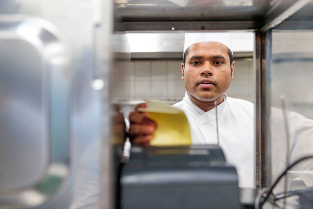 Chef Reviewing the Order Received from the Restaurant stock photo