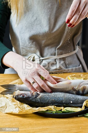 496065234istockphoto Chef salted sea bass on a wooden table. Black background, side view, space for text. 1136550681
