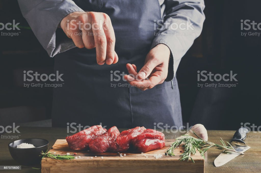 Chef seasoning filet mignon on wooden board at restaurant kitche stock photo