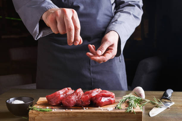 Chef seasoning filet mignon on wooden board at restaurant kitchen stock photo