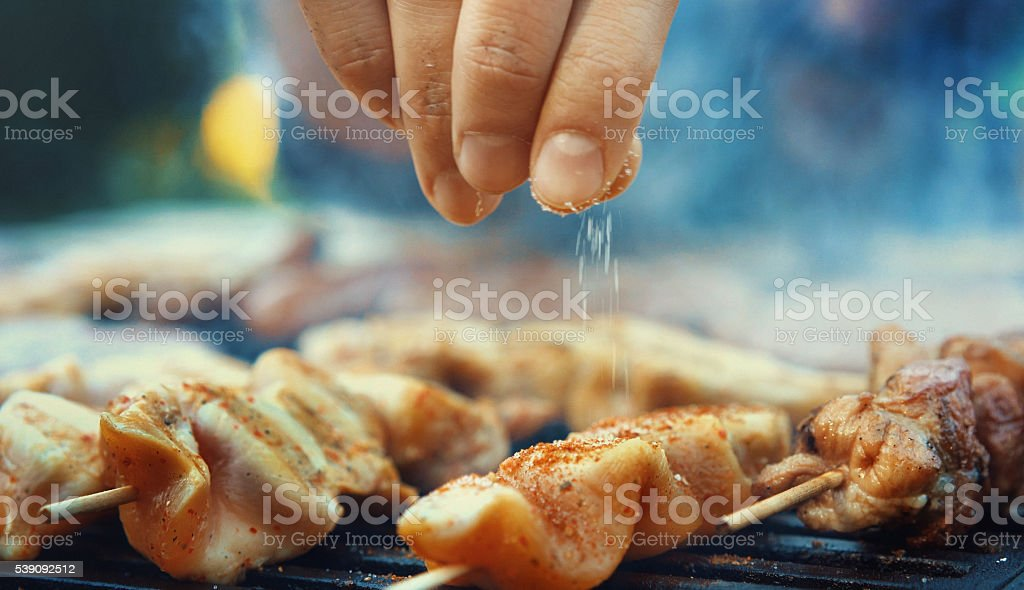 Chef seasoning meat on a grill. stock photo